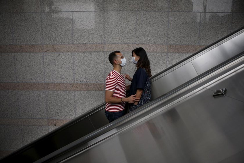 A couple wearing masks to prevent contracting Middle East Respiratory Syndrome (MERS) looks at each other as they ride on an escalator in Seoul