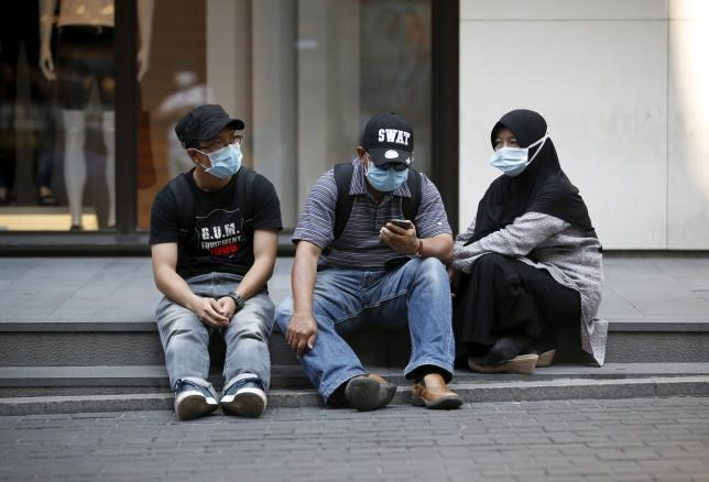Tourists wearing masks to prevent contracting Middle East Respiratory Syndrome (MERS) rest at Myeongdong shopping district in central Seoul, South Korea, June 12, 2015.