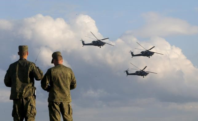 Russian servicemen watch Mi-28 military helicopters of the Berkuti (Golden Eagles) aerobatic team fly during the opening of the Army-2015 international military forum in Kubinka, outside Moscow, Russia, June 16, 2015.