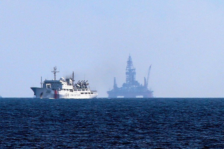 A Chinese coast guard ship navigates in front of Chinese drilling equipment located in waters off the Paracel Islands. Source: The Asahi Shimbun via Getty Images