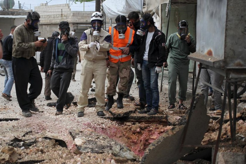 Civil Defence members wear gas masks near damaged ground in Ibleen village from what activists said was a chlorine gas attack, on Kansafra, Ibleen and Josef villages, Idlib countryside May 3, 2015.
