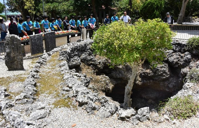 Students look at a cave used as a field hospital during World War II at the Himeyuri Peace Museum in Itoman, Okinawa prefecture, on June 19, 2015.