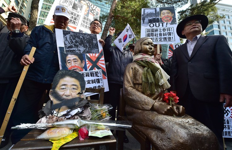 South Korean protesters stand next to a statue of a diminutive Korean girl outside the Japanese embassy in Seoul. Photo: AFP