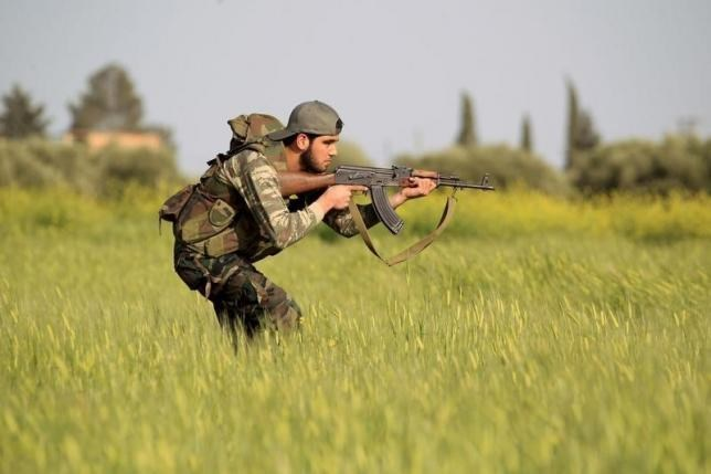A rebel fighter aims his weapon as he takes a position during a military training in Aleppo's countryside against forces loyal to Syria's President Bashar al-Assad April 20, 2015.