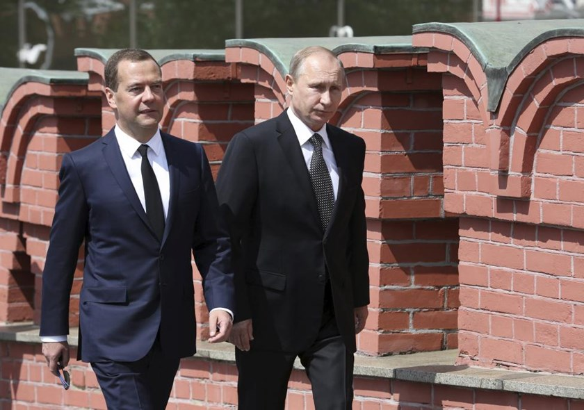 Russian President Vladimir Putin (R) and Prime Minister Dmitry Medvedev walk to attend a wreath-laying ceremony at the Tomb of the Unknown Soldier in central Moscow, Russia, June 22, 2015.