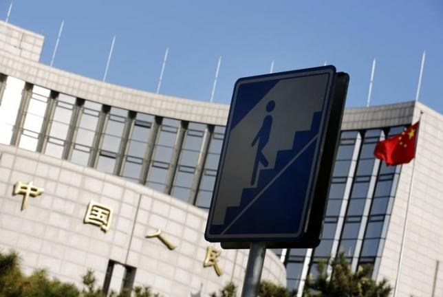 A sign for pedestrians is seen in front of the headquarters of the People's Bank of China, China's central bank, in central Beijing November 24, 2014.