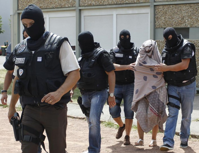 French special police forces escort a woman from a residential building during a raid in Saint-Priest, near Lyon, France, June 26, 2015.