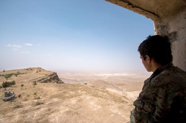 A Kurdish People's Protection Units (YPG) fighter stands on a lookout point on Abd al-Aziz mountain, Hasaka province May 20, 2015.