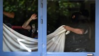 Special forces of France's Research and Intervention Brigades (BRI) cover a window with a sheet as they search the apartment of a man suspected of carrying out an attack in Saint-Priest. Photo: AFP