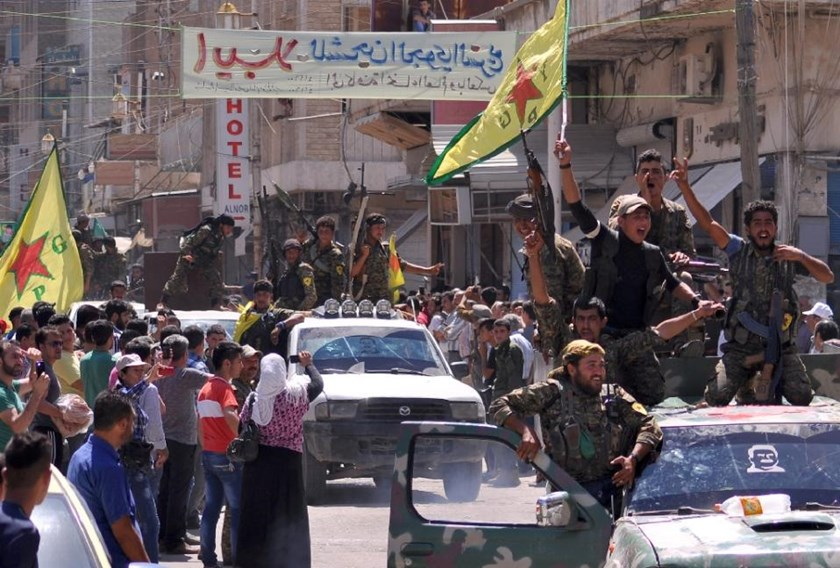 Kurdish People's Protection Units fighters cheer as they parade on June 24, 2015 in the northeastern Syrian town of Qamishli after returning from battling Islamic State group jihadists in Tal Abyad.