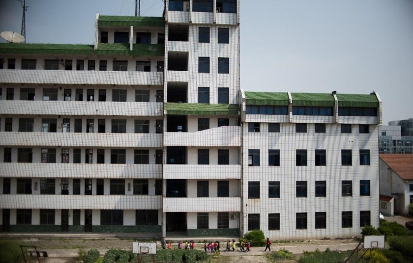 The once-bustling The once-bustling Technical Secondary School in Rudong, Jiangsu province, now a hollow shell looms, over a small group of pupils in the playground