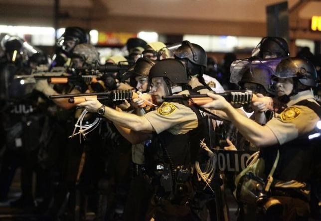 Police officers point their weapons at demonstrators protesting against the shooting death of Michael Brown in Ferguson, Missouri August 18, 2014.