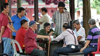 Elderly people gather to play a checkers game next to their housing area in Singapore on January 2, 2013