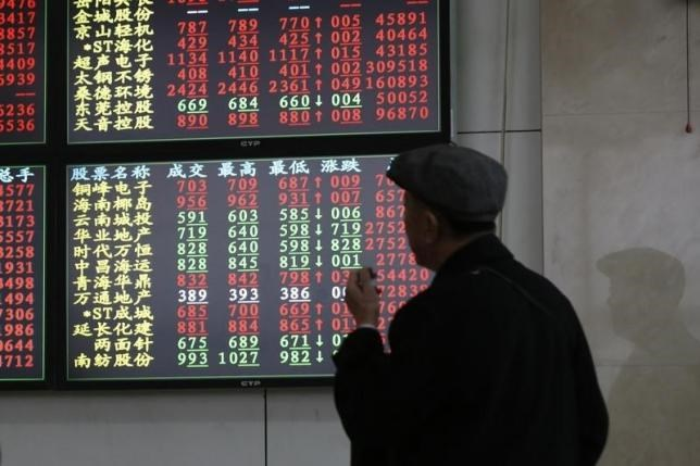 An investor looks at information displayed on an electronic screen at a brokerage house in Shanghai, November 17, 2014.