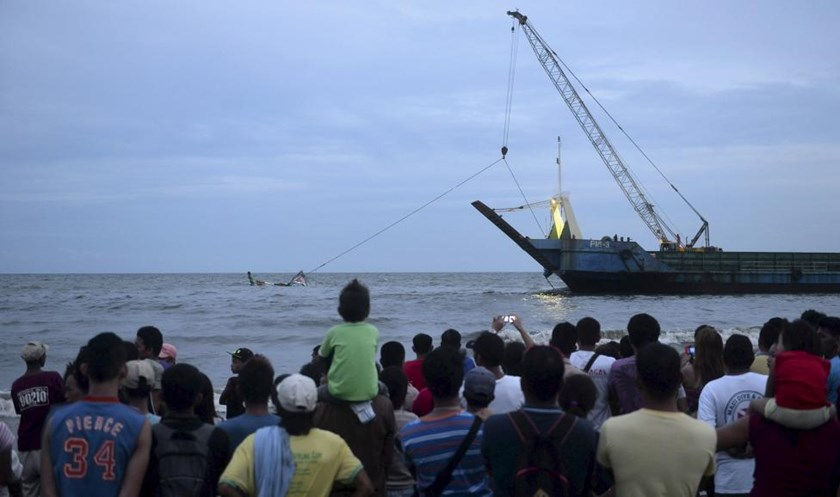 Residents and relatives of victims watch members of the Philippine Coast Guard attempting to recover the remains of the capsized vessel MBCA Kim-Nirvana during a search and rescue operations near a port in Ormoc city, central Philippines July 2, 2015.