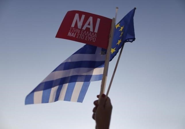 A 'Yes' supporter waves a Greek flag on arrival for the pro-Euro rally at the Panathenean stadium in Athens, Greece, July 3, 2015.