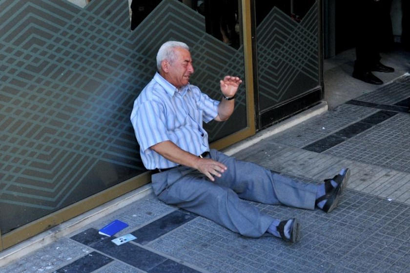 Distressed Greek pensioner, Giorgos Chatzifotiadis, sits on the ground outside a national bank branch in Thessaloniki, on July 3, 2015