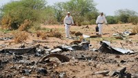 Forensics gather evidence at the crash site of the Air Algerie flight AH5017 in Mali's Gossi region on July 29, 2014