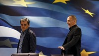 Outgoing Finance Minister Yanis Varoufakis (R) shows newly-appointed Finance Minister Euclid Tsakalotos his chair at the Finance Ministry before a handover ceremony in Athens, Greece July 6, 2015.