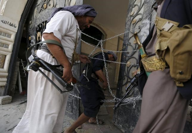 Guards walk through a damaged gate of the house of Brigadier Khaled al-Anduli, an army commander loyal to the Houthi movement, after it was hit by Saudi-led air strikes in Yemen's capital Sanaa July 6, 2015