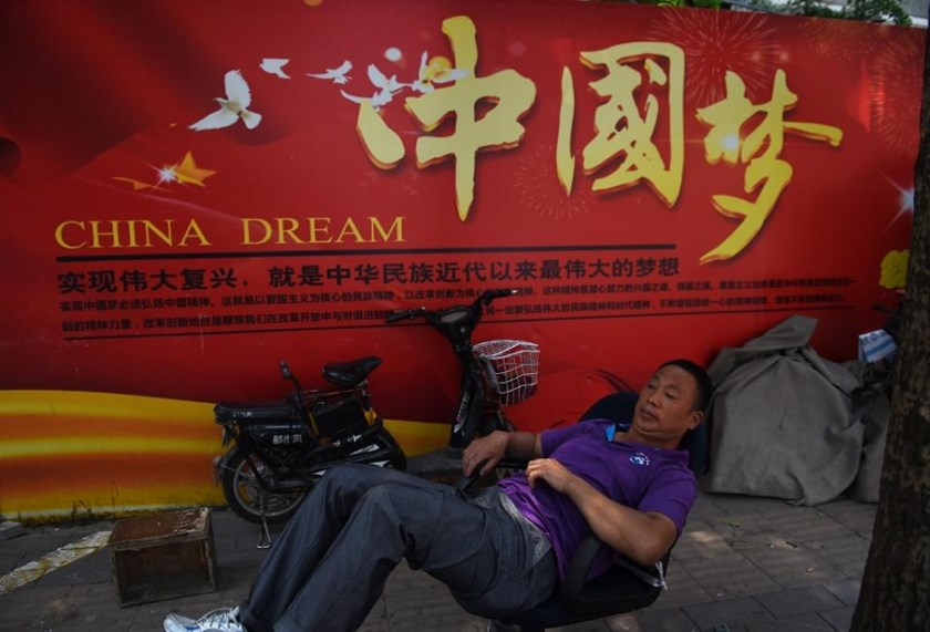 "A man rests in Beijing on July 7, 2015, in front of a banner about President Xi Jinping's vision for China's future, with characters translating as ""To realise the revitalisation is the biggest dream in modern times of Chinese nationals."""