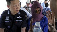 Police Major General Thatchai Pitaneelaboot (L) listens as a Rohingya trafficking victim leads a police unit to a camp where he was detained in Satun, southern Thailand in this March 27, 2014 file photo.