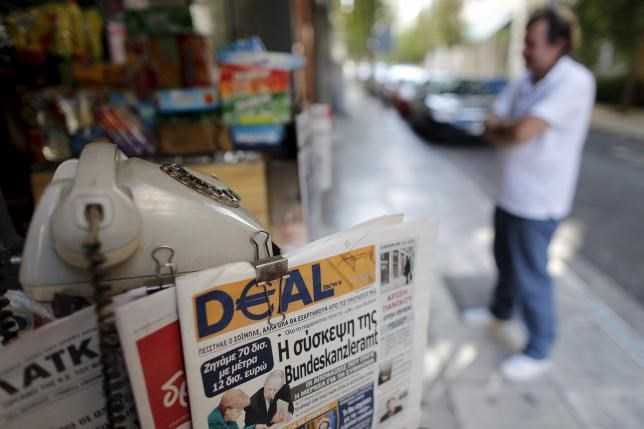 A vendor waits for clients in front of a newspaper kiosk in central Athens, Greece, July 12, 2015.