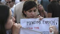 Youths hold a placard that reads 'Do we stay in Euro?' during an anti-austerity protest in central Athens, Greece, July 12, 2015.
