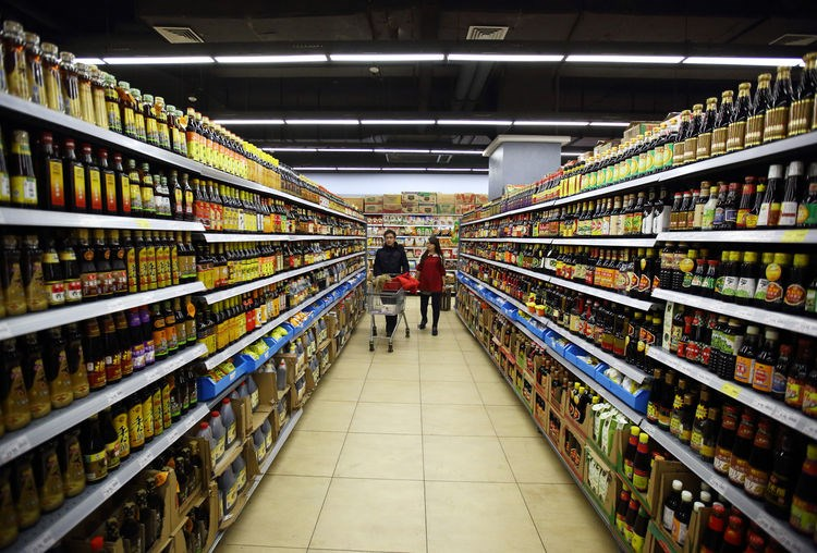 Shoppers browse in the condiments section of a supermarket in Beijing, China.