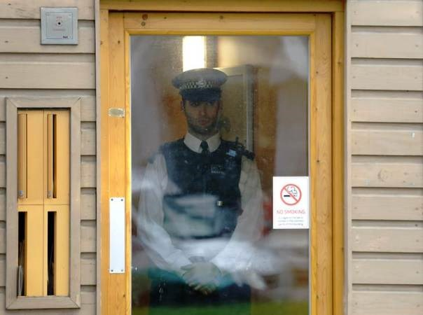 "Police stand guard at a property in Lambeth, south London November 23, 2013. Three women enslaved in London for 30 years appeared to have been part of a cult and bound to their captors by ""invisible handcuffs"" through beatings and brainwashing, police said on Saturday."
