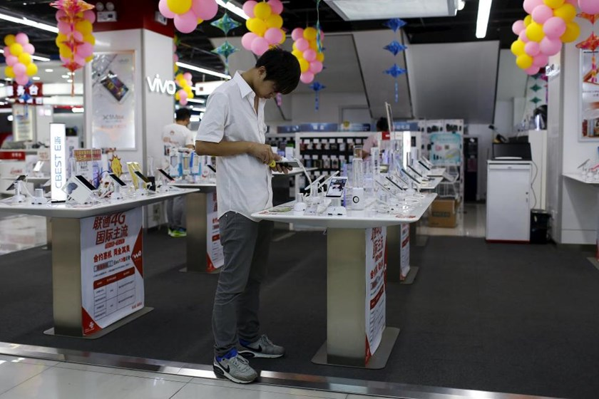 A customer look at a mobile phone on display at an electronics market in Shanghai, China, June 24, 2015. Picture taken June 24, 2015.