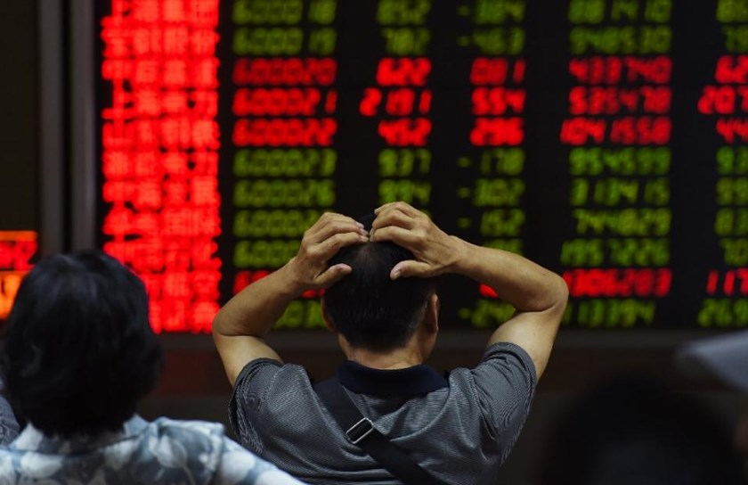 An investor looks at screens showing stock market movements at a securities company in Beijing on July 14, 2015.