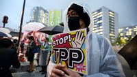 A man holds a placard as he takes part in a protest against Trans-Pacific Partnership (TPP) trade talks outside the prime minister's official residence in Tokyo, Japan in April 2014. Photo: Bloomberg