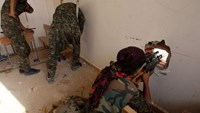 Members of the Kurdish People's Protection Units (YPG) defend a classroom in the village of Maarouf in the northeastern Syrian province of Hasakeh on July 16, 2015, as they battle Islamic State group jihadists
