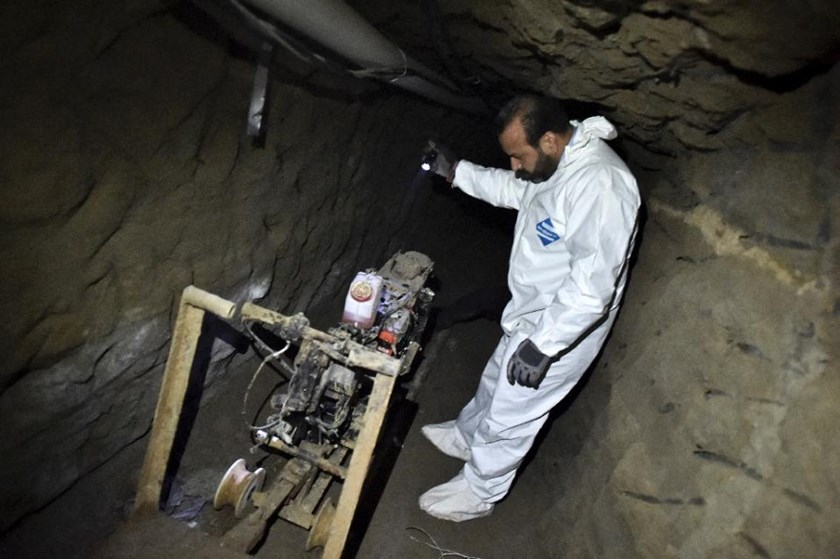 "An investigator looks at a motorcycle rigged on a special rail system in the tunnel through which Mexican drug lord Joaquin ""El Chapo"" Guzman escaped from the Altiplano prison in Almoloya de Juarez, Mexico, on July 15, 2015"
