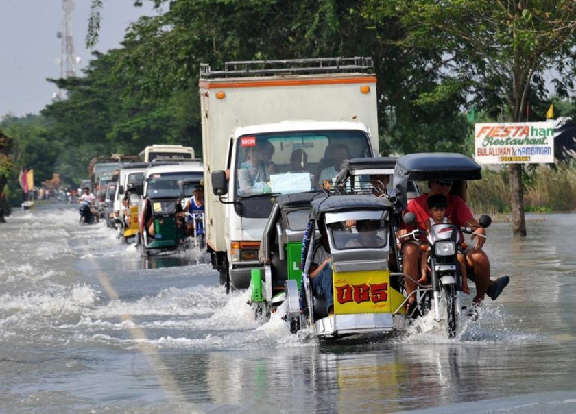 Motorists traverse a flooded highway in the town of Rosales, Pangasinan province north of Manila on October 11, 2009