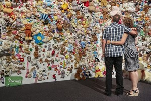 Relatives of those killed when flight MH17 was shot down over Ukraine gather in front of an 'hedge of compassion' made of thousands of dolls in Nieuwegein on July 17, 2015