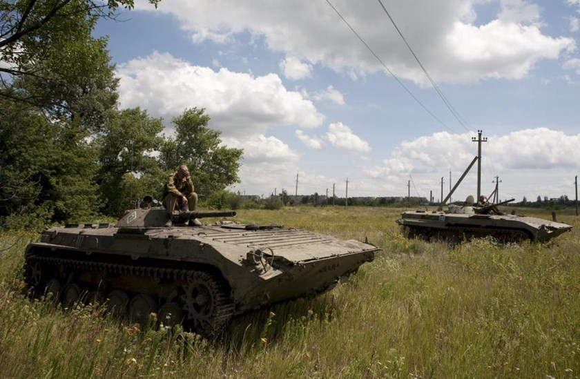 Members of the self-proclaimed Donetsk People's Republic forces sit on armored vehicles after withdrawing them further from the frontline in a field on the suburbs of Debaltseve in Donetsk region, Ukraine, July 21, 2015.
