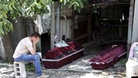 A man, whose mother according to locals was killed by an early morning shelling, reacts while sitting near her coffin, outside the damaged house before her funeral in Donetsk, Ukraine, in this July 7, 2015 file photo.