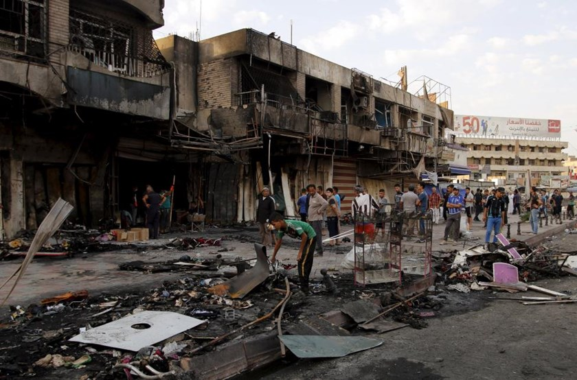People gather at the site of car bomb in New Baghdad, July 22, 2015.