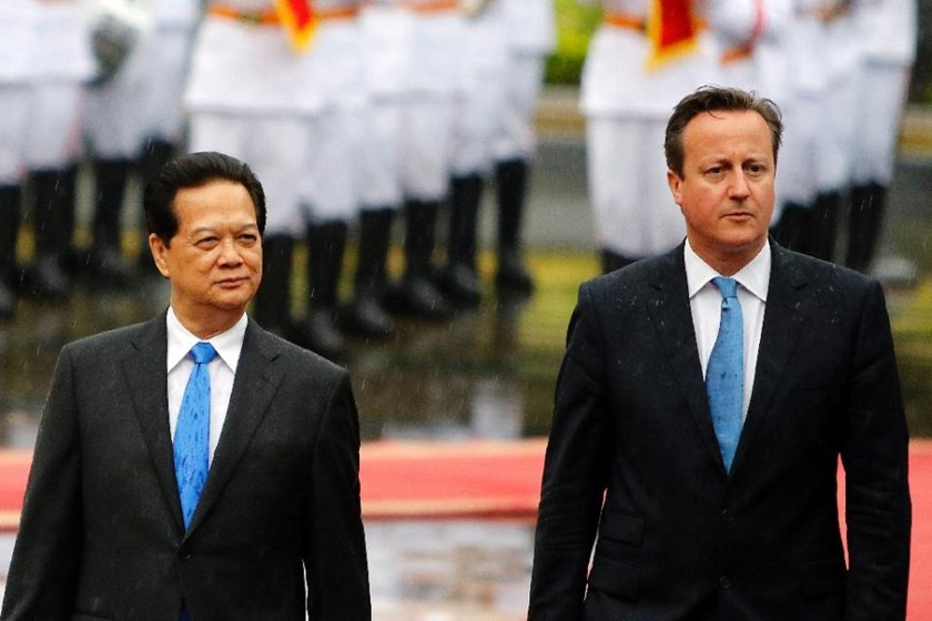 Prime Minister David Cameron (right) and his Vietnamese counterpart Nguyen Tan Dung review an honour guard during a welcoming ceremony at the presidential palace in Hanoi on July 29, 2015.