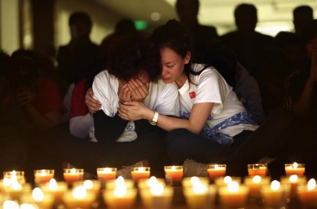 A family member cries as she and other relatives pray during a candlelight vigil for passengers onboard the missing Malaysia Airlines Flight MH370 in the early morning, at Lido Hotel, in Beijing April 8, 2014.