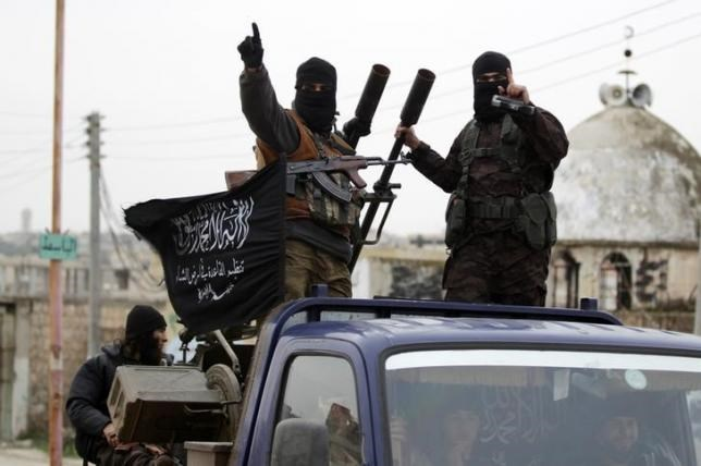 Members of al Qaeda's Nusra Front gesture as they drive in a convoy touring villages, which they said they have seized control of from Syrian rebel factions, in the southern countryside of Idlib, December 2, 2014. Picture taken December 2, 2014.