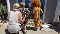 Sarah Madison (L) holds her son Beckett, 3, as her daughter Quinn, 5 (in costume), look at stuffed animals at the doorway of River Bluff Dental clinic in protest against the killing of ''Cecil'' a famous lion in Zimbabwe, in Bloomington, Minnesota July 29, 2015.