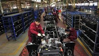 Workers install the chassis along a production line at a truck factory of Anhui Jianghuai Automobile Co. Ltd (JAC Motors) in Hefei, Anhui province May 5, 2014.