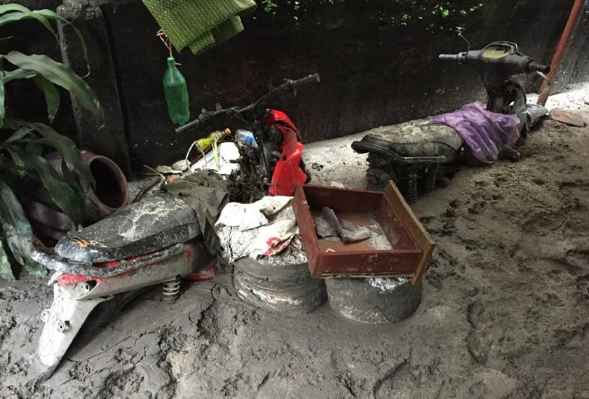 Motorcycles seen buried in think mud in a community located next to the Mong Duong coal mine on August 1, 2015 following heavy rains in the northern coastal province of Quang Ninh