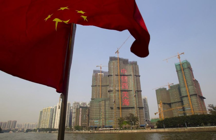 A Chinese national flag flutters on the Pearl River near a construction site in Guangzhou, Guangdong province, in this March 27, 2014 file photo.