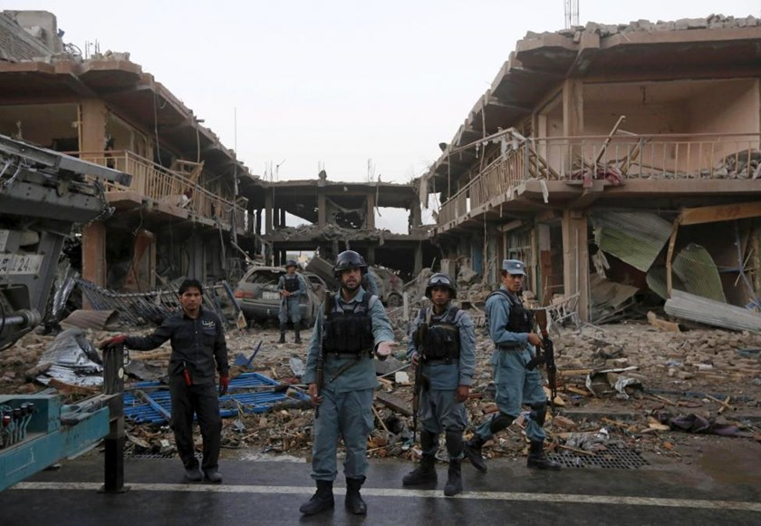 Afghan policemen stand guard at the site of a suicide truck bomb in Kabul, Afghanistan August 7, 2015.