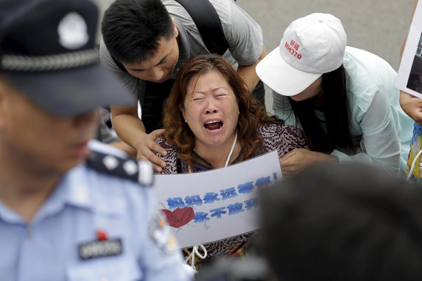 A woman whose relative was aboard Malaysia Airlines flight MH370, holds a placard that reads, 'Mom is always here waiting for you, never will give up', as she cries next to family members and kneels down in front of media ahead of a briefing given by Malaysia Airlines