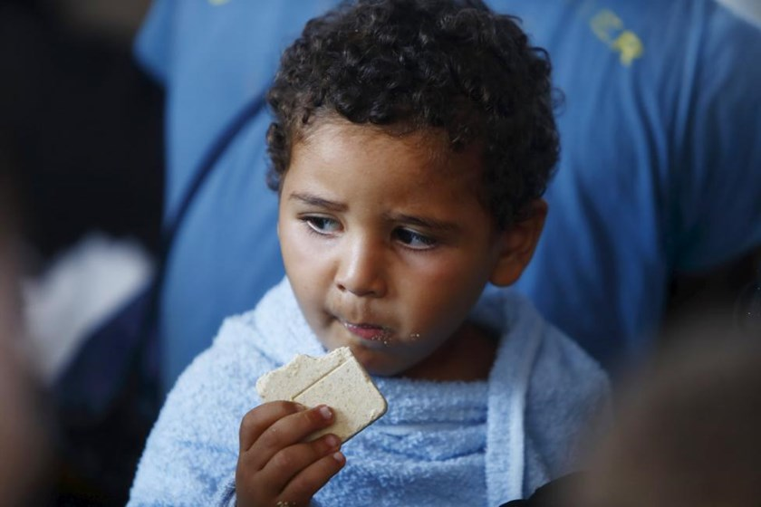 A migrant child eats emergency ration food on the Migrant Offshore Aid Station (MOAS) ship MV Phoenix after being rescued from an overloaded wooden boat 10.5 miles (16 km) off the coast of Libya August 6, 2015.